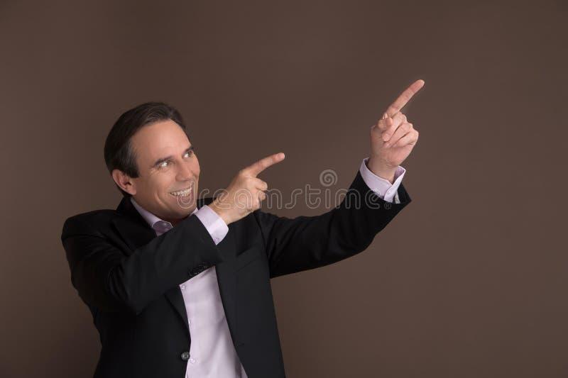 El señalar lejos con entusiasmo. Punto maduro alegre del hombre de negocios foto de archivo libre de regalías