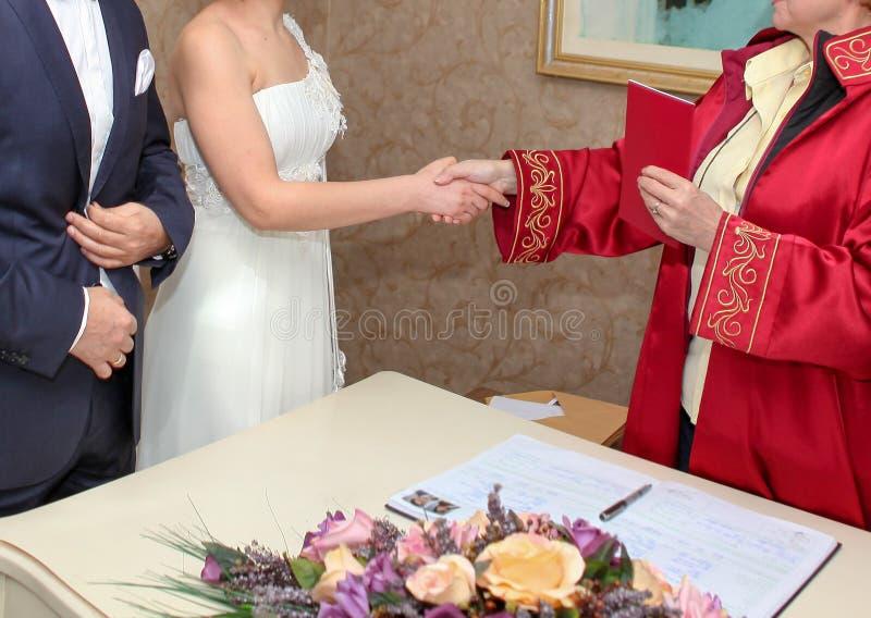 El secretario del matrimonio felicita nuevos pares y da el registro de la familia a la novia imágenes de archivo libres de regalías
