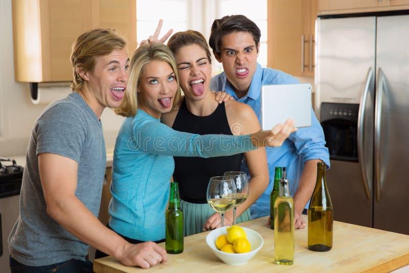 El selfie divertido torpe hace frente a la gente de los amigos junto que se divierte en un partido fotografía de archivo