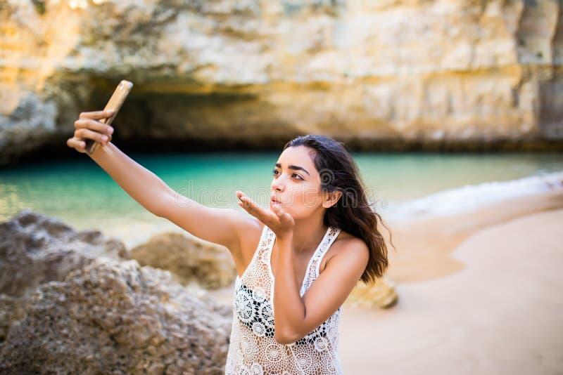 El selfie latino hermoso de la toma de la muchacha en el teléfono en las cuevas hermosas vara cerca del océano Concepto de la voc fotografía de archivo libre de regalías
