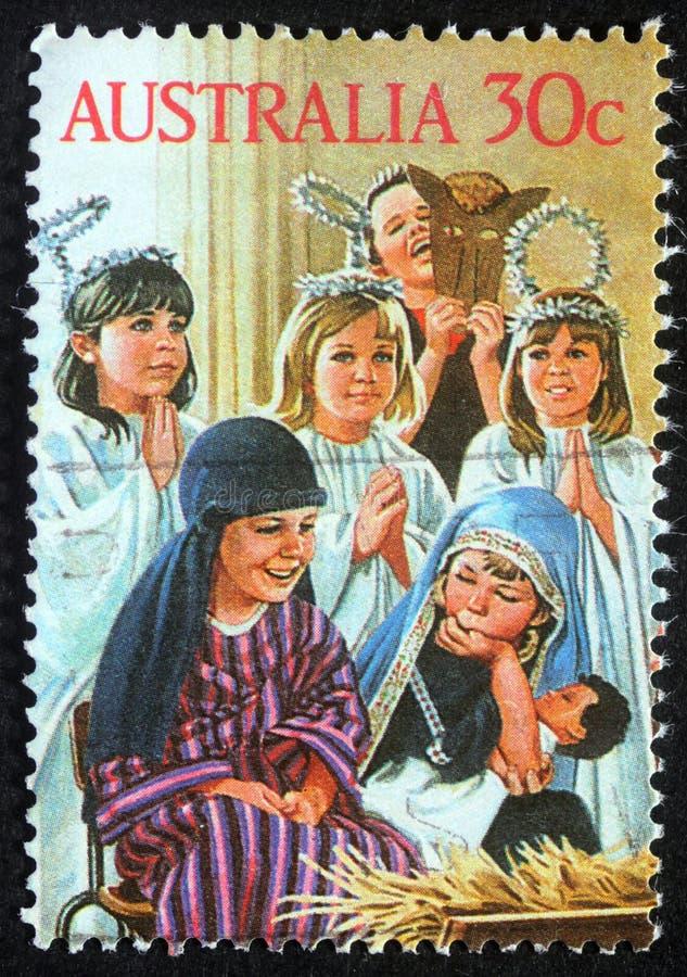 El sello de la Navidad impreso en Australia muestra el juego de niños a la familia santa foto de archivo libre de regalías