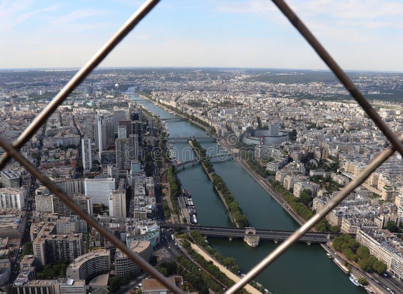 El Sena y la París a través de las barras de la torre Eiffel imagen de archivo libre de regalías