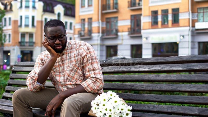 El sentarse afroamericano trastornado del hombre solo en banco de la ciudad con el ramo, fallado fecha fotografía de archivo