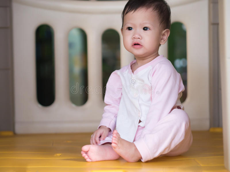 El sentarse asiático del niño interior Mirada lejos fotos de archivo