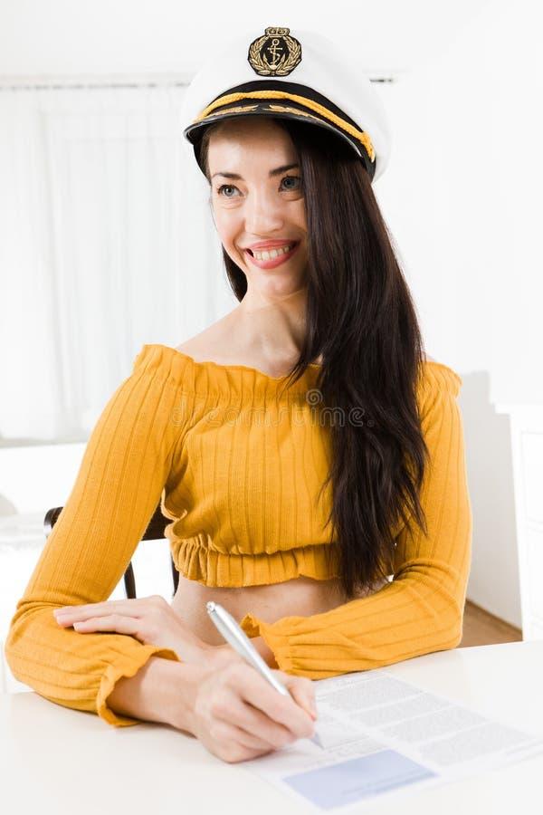 El sentarse atractivo de la mujer y tabla blanca y escritura con la sonrisa del nd del pena imagen de archivo libre de regalías
