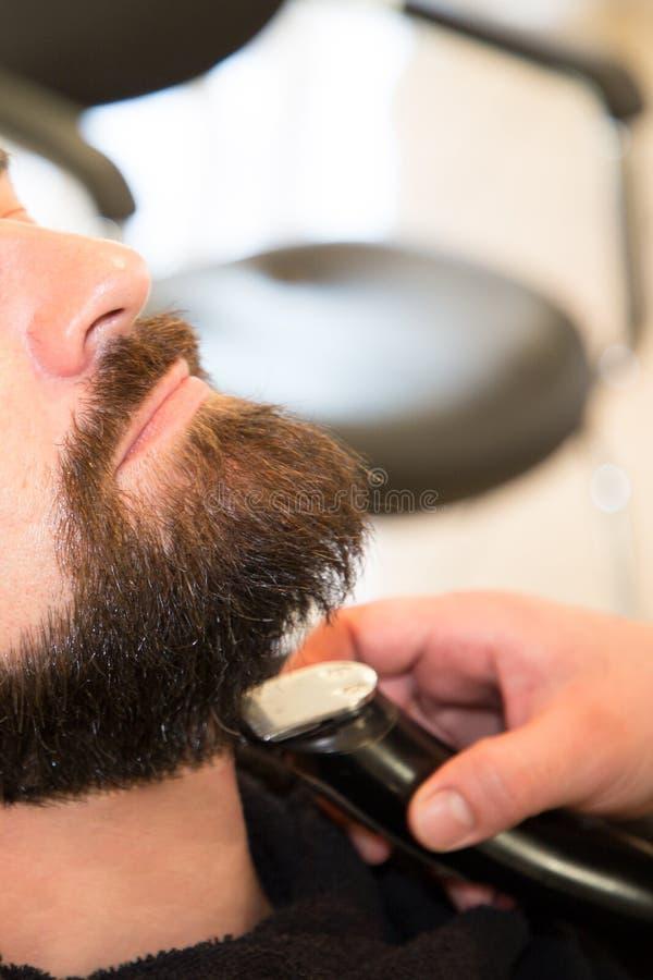 El sentarse barbudo del hombre relajado en la barbería por la barba profesional del ajuste del peluquero foto de archivo