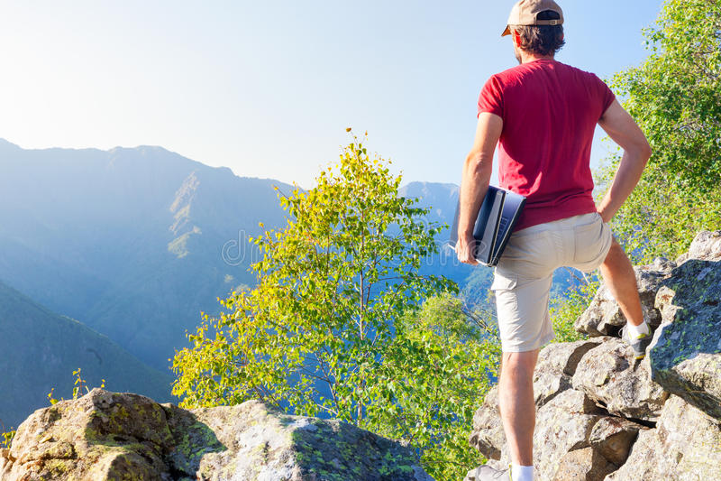 El sentarse caucásico joven del hombre al aire libre en una roca que trabaja en un lapto imagen de archivo