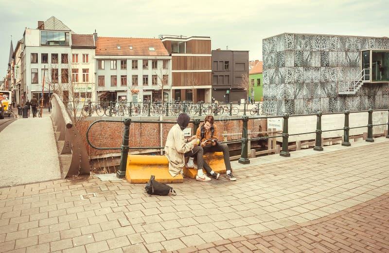 El sentarse de dos estudiantes libros al aire libre, el hablar y de lectura fotografía de archivo