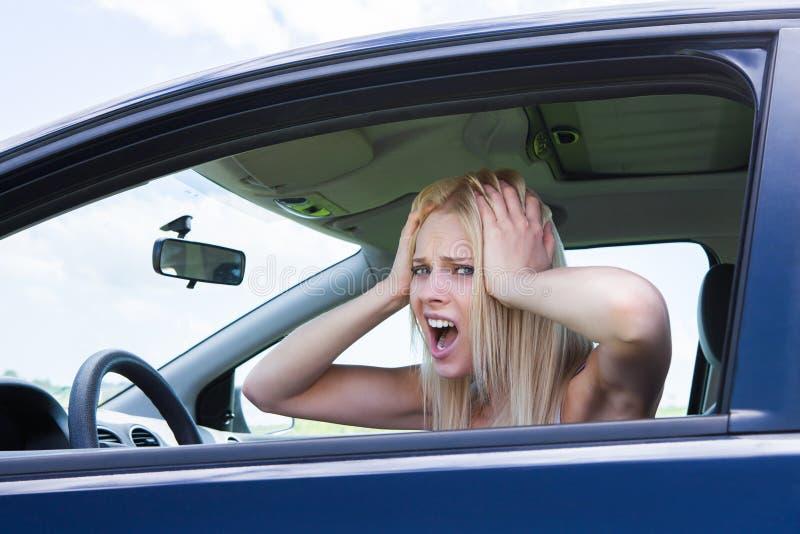 El sentarse de griterío frustrado de la mujer en coche foto de archivo