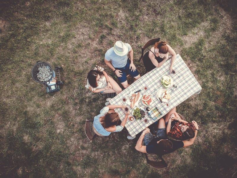 El sentarse de la gente al aire libre en la tabla que celebra el partido en los campos fotografía de archivo libre de regalías
