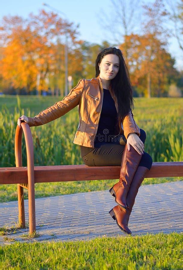 el sentarse de la muchacha al aire libre en paisaje del otoño foto de archivo