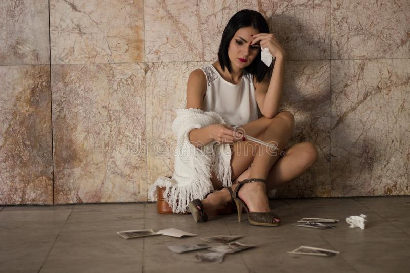 El sentarse de la mujer solo y deprimido imagenes de archivo