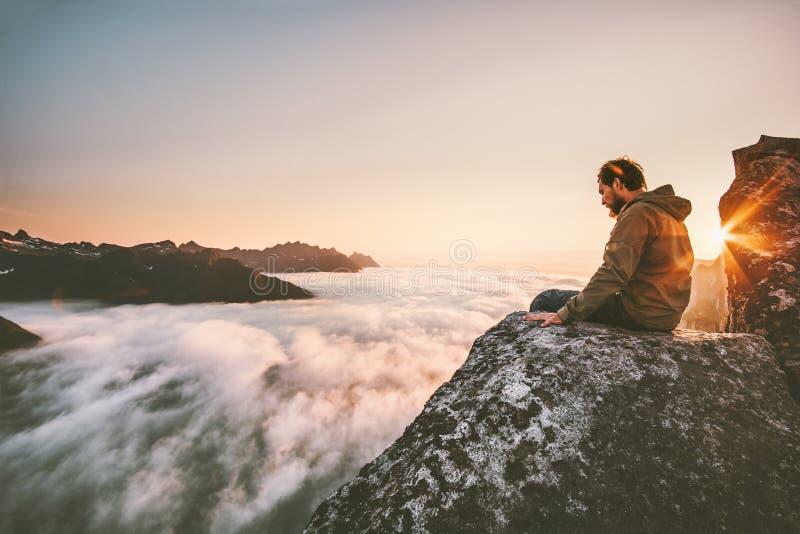 El sentarse de pensamiento del hombre solamente en el top de la montaña del borde del acantilado fotos de archivo