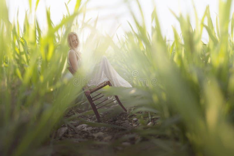 el sentarse de reclinación de la mujer miniatura entre los penachos gigantescos de la hierba imagen de archivo libre de regalías