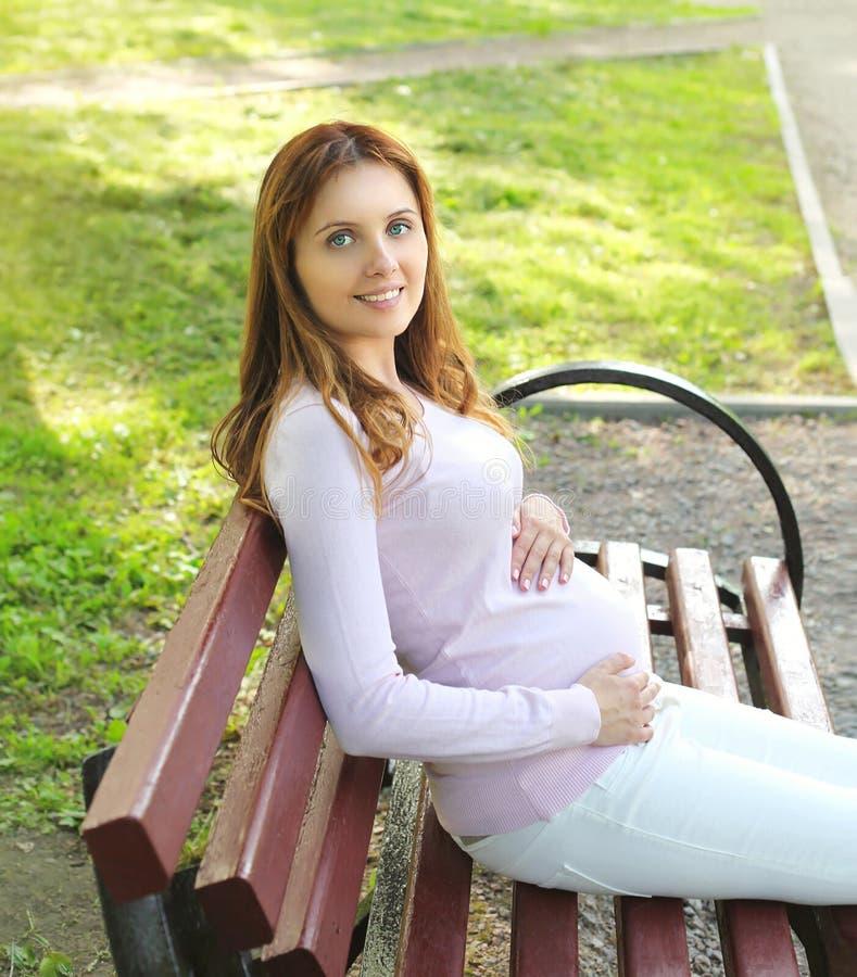 El sentarse de reclinación sonriente de la mujer embarazada de los jóvenes felices foto de archivo libre de regalías