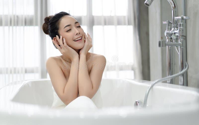 El sentarse de relajaci?n de la mujer asi?tica joven hermosa en el bathtube en el cuarto de ba?o Tratamientos del balneario para  imagen de archivo