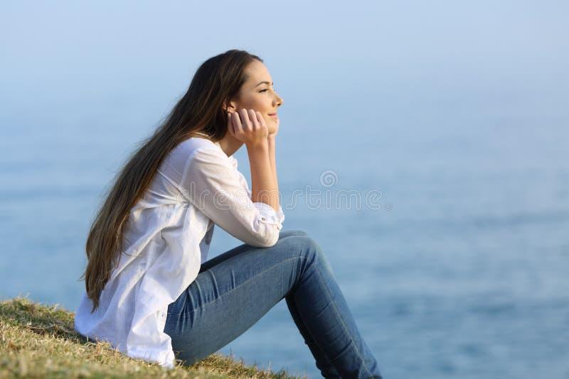 El sentarse de relajación de la mujer en la hierba que mira el mar fotografía de archivo