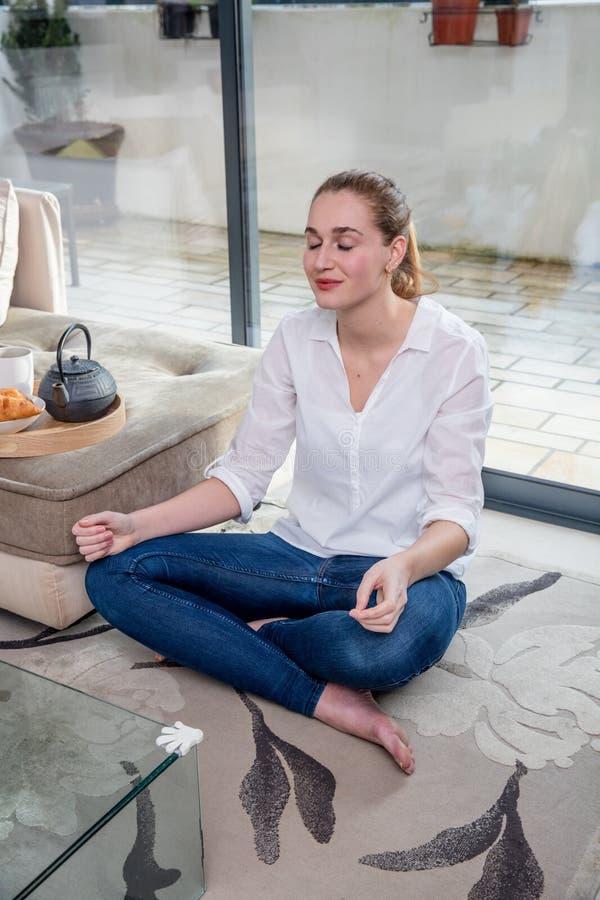 El sentarse de relajación sonriente de la mujer joven en la posición de loto respecto a piso fotos de archivo