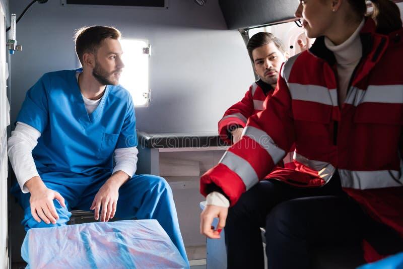 El sentarse de tres doctores de la ambulancia imágenes de archivo libres de regalías
