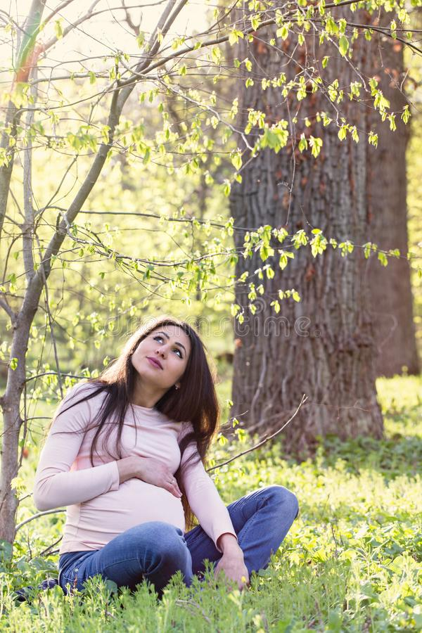 El sentarse debajo de un árbol de la primavera foto de archivo