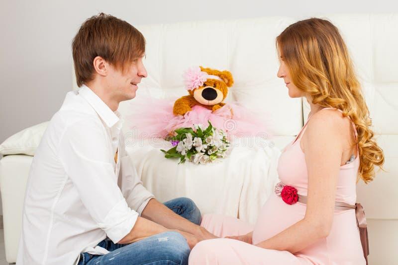 El sentarse del hombre y de la mujer embarazada cara a cara fotos de archivo libres de regalías