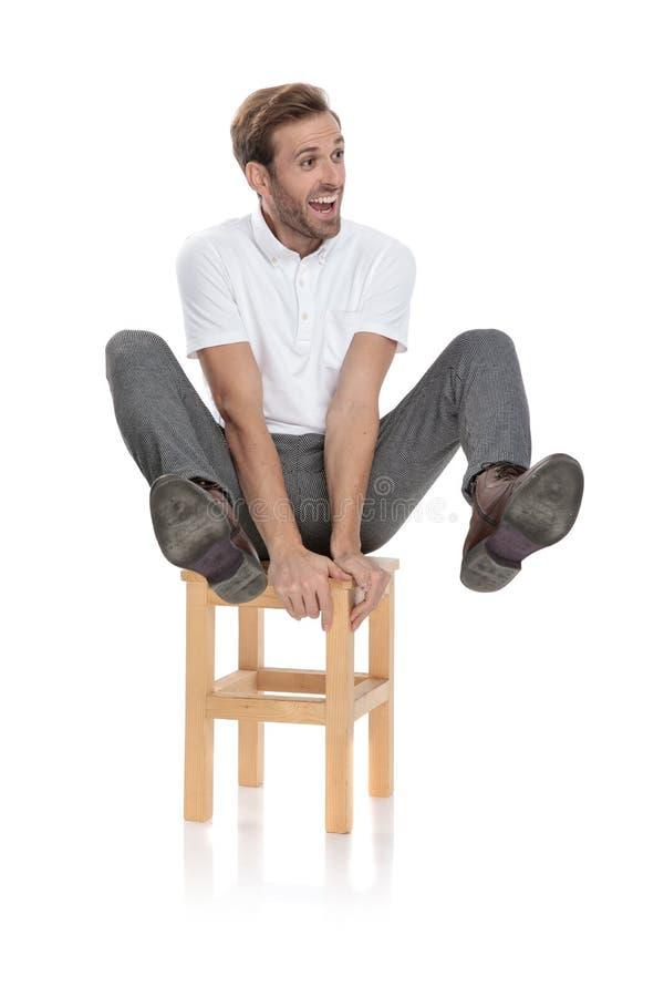 El sentarse del hombre y piernas casuales locos de los controles en el aire fotos de archivo