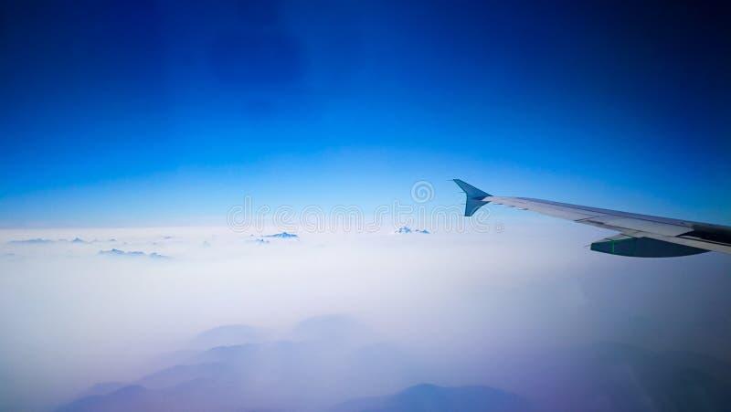El sentarse en el avión para ver el mar de nubes y los picos del mar imágenes de archivo libres de regalías