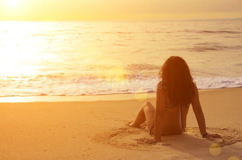 El sentarse en la arena foto de archivo libre de regalías
