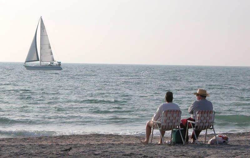 El sentarse en la playa fotografía de archivo