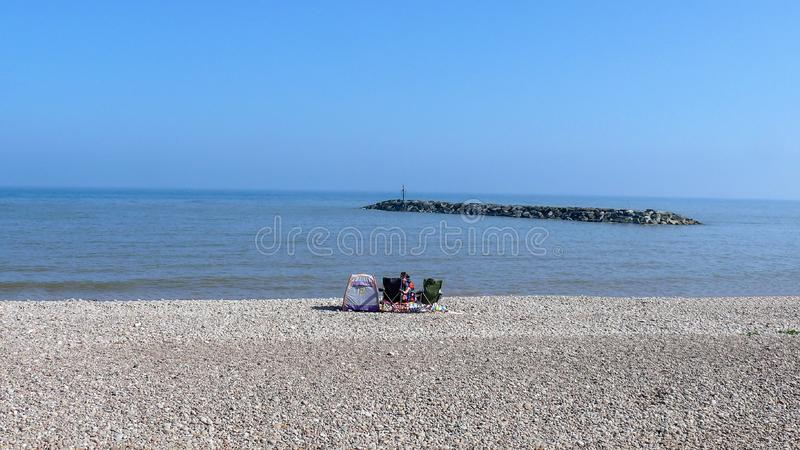El sentarse en la playa en Sidmouth imagen de archivo libre de regalías