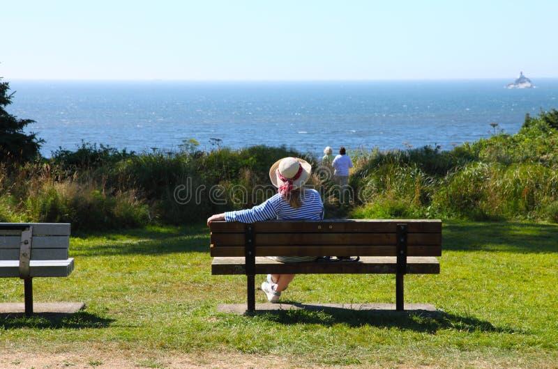 El sentarse en un banco que mira el Océano Pacífico. imagen de archivo libre de regalías