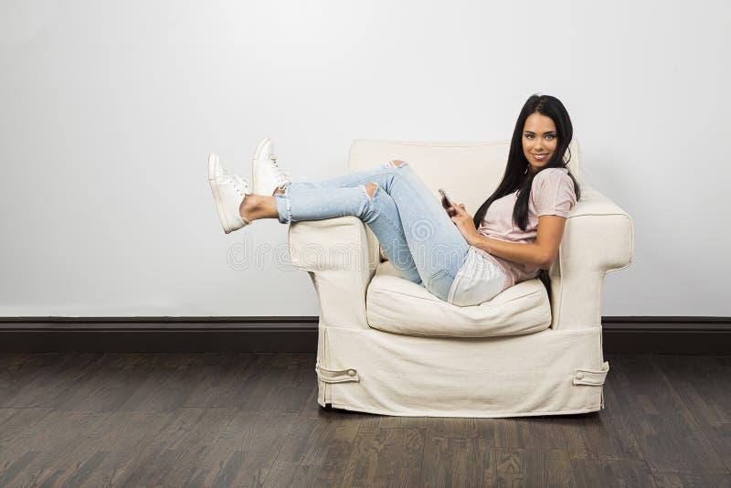 El sentarse en un sofá blanco con el teléfono imagen de archivo libre de regalías