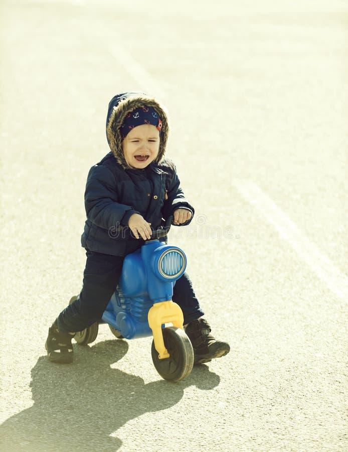 El sentarse gritador del niño o del pequeño muchacho en el coche de motor del juguete fotografía de archivo