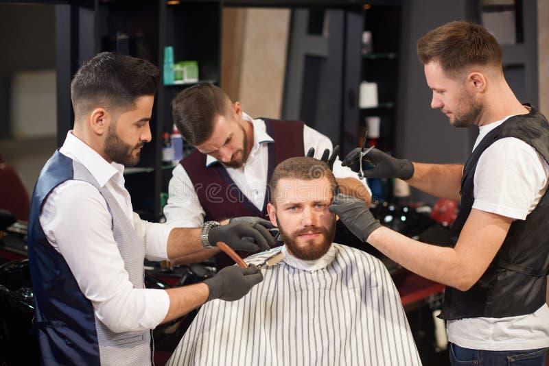 El sentarse masculino en silla mientras que peluqueros que lo mantienen imagen de archivo