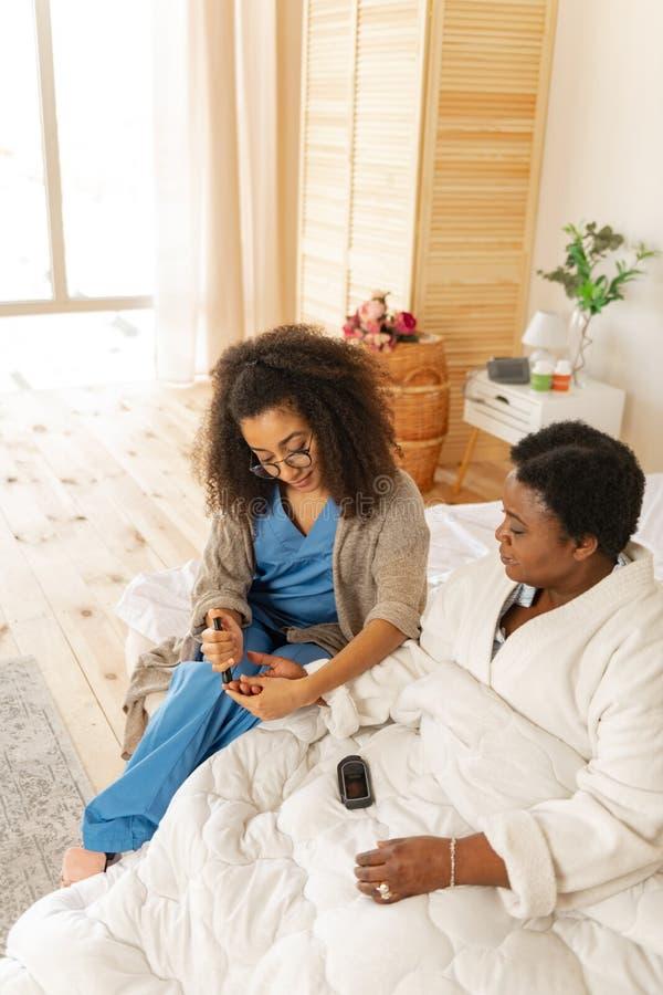 El sentarse paciente en cama cerca de la enfermera que toma los hemogramas para ella fotografía de archivo