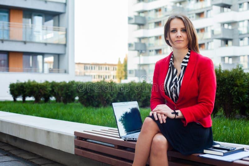 El sentarse profesional joven de la mujer de negocios al aire libre con el ordenador imágenes de archivo libres de regalías