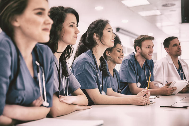 El sentarse que escucha de los estudiantes de medicina en el escritorio fotografía de archivo libre de regalías
