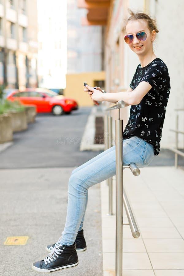 El sentarse que se inclina de la muchacha adolescente en la barandilla y usar el teléfono celular fotos de archivo