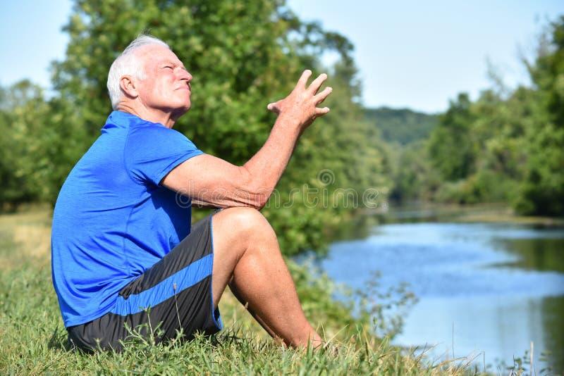 El sentarse que se pregunta masculino adulto atlético por el río fotos de archivo