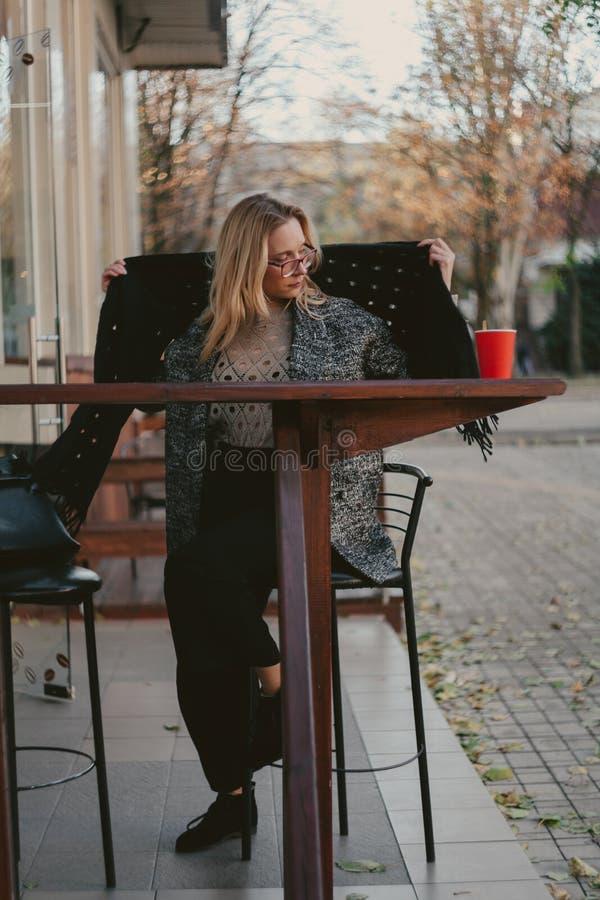 El sentarse rubio elegante en café de la calle imágenes de archivo libres de regalías