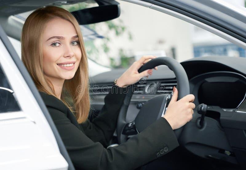 El sentarse rubio en el nuevo automóvil, comprador del coche imagenes de archivo