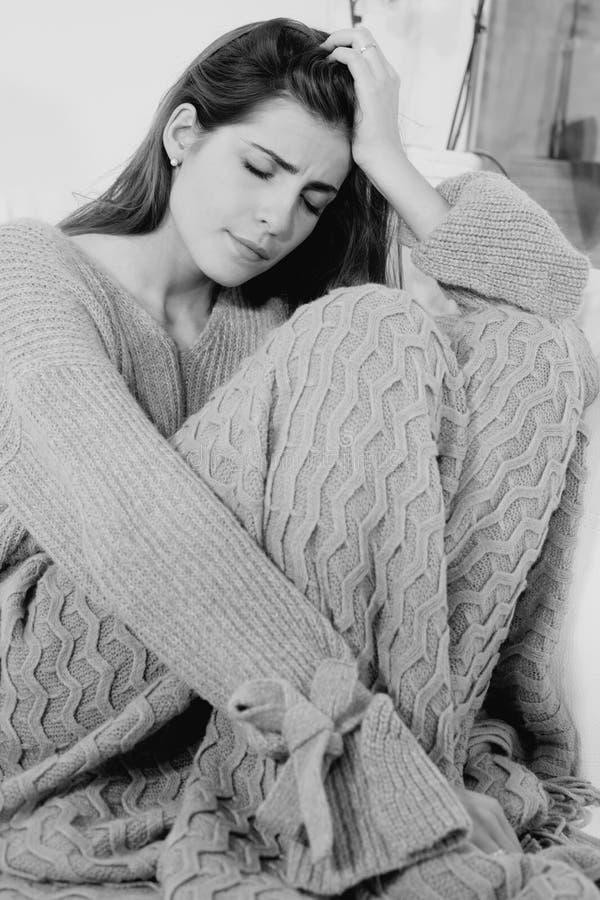 El sentarse solo de la sensación triste de la mujer en casa en tiro medio del sofá foto de archivo