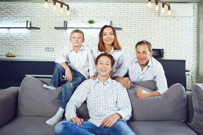 El sentarse sonriente de la familia feliz en el sofá en sitio fotografía de archivo libre de regalías