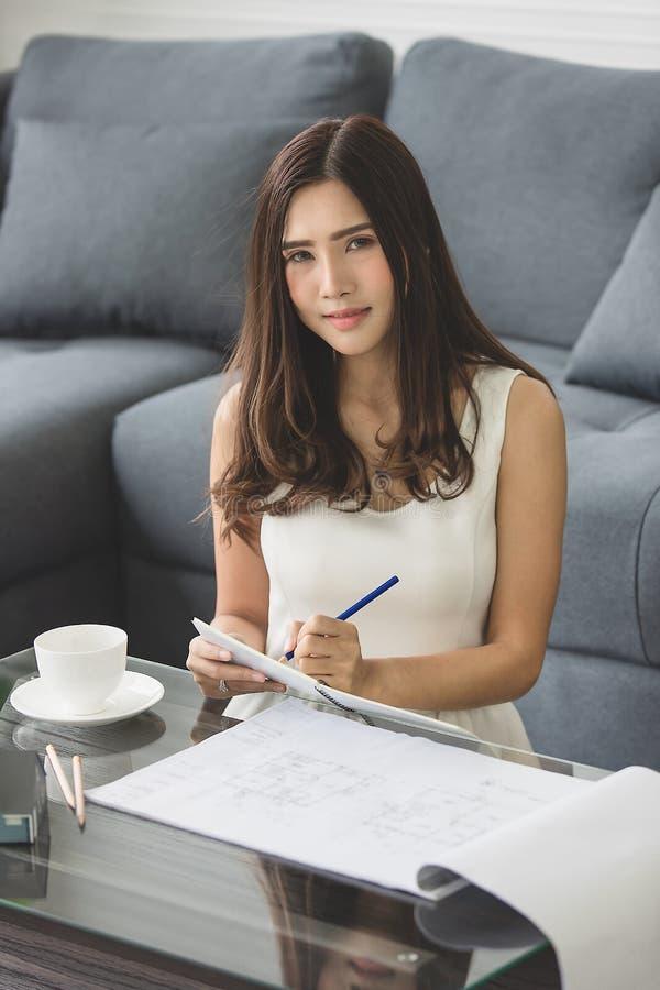 El sentarse sonriente de la muchacha asiática hermosa en el sofá de casero de trabajo foto de archivo libre de regalías