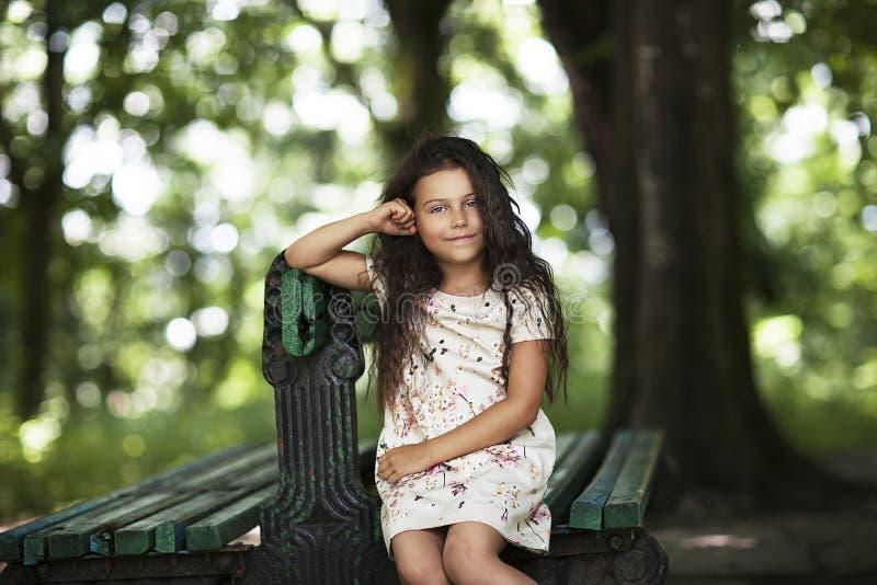 El sentarse sonriente de la muchacha hermosa en el banch en el parque imagen de archivo libre de regalías