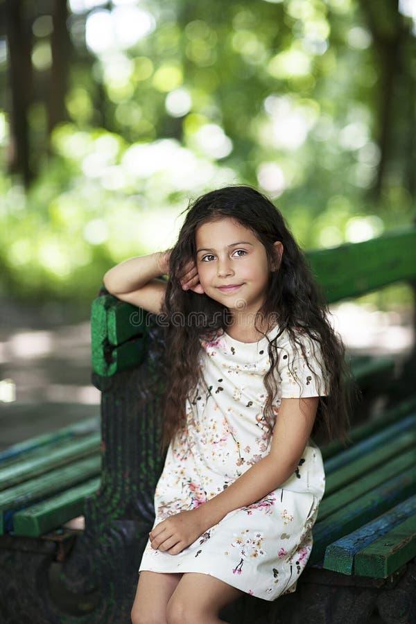 El sentarse sonriente de la muchacha hermosa en el banco en el parque fotos de archivo