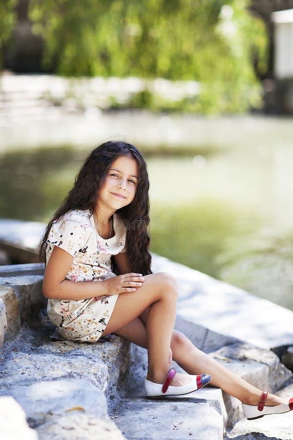 El sentarse sonriente de la muchacha hermosa en las escaleras en el parque fotografía de archivo libre de regalías