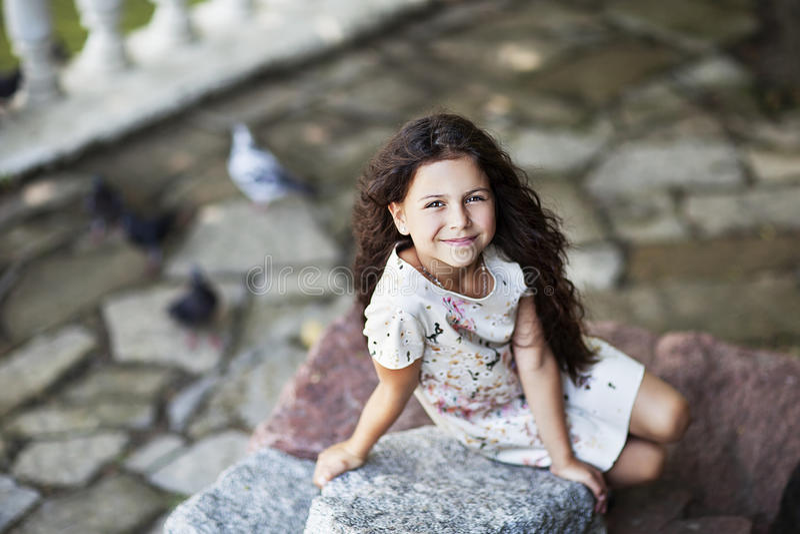 El sentarse sonriente de la muchacha hermosa en roca en el parque fotografía de archivo