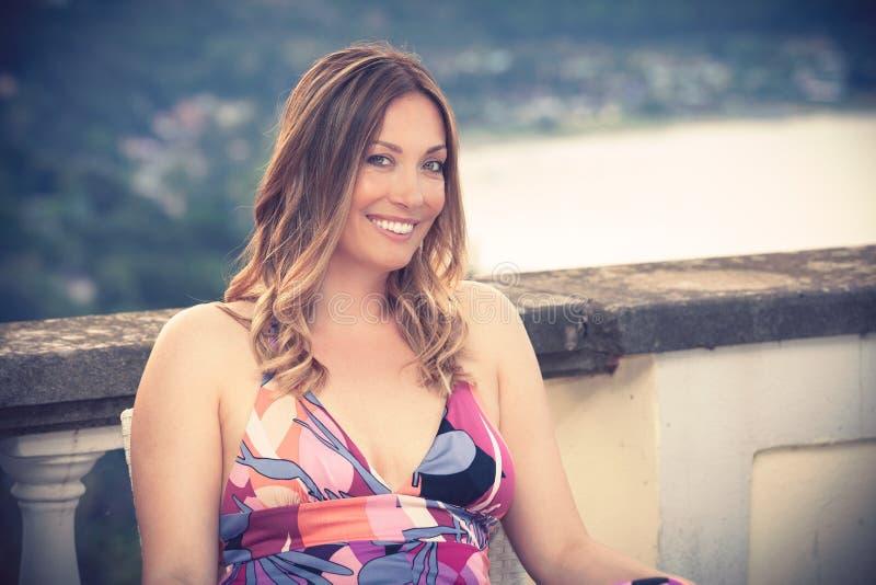 El sentarse sonriente hermoso y encantador de la mujer al aire libre foto de archivo libre de regalías