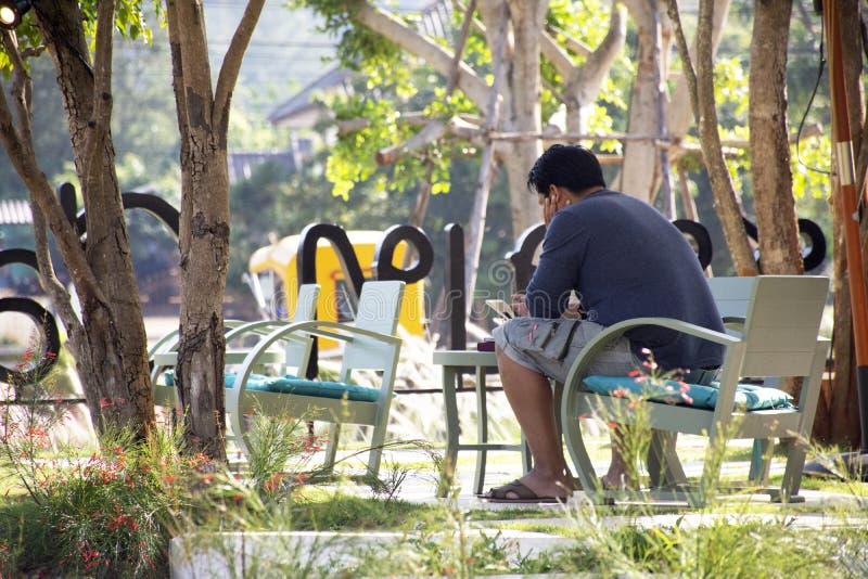 El sentarse tailandés del hombre de los viajeros relajado con muebles de la decoración y el diseño exterior de cafetería en Nakho fotografía de archivo libre de regalías